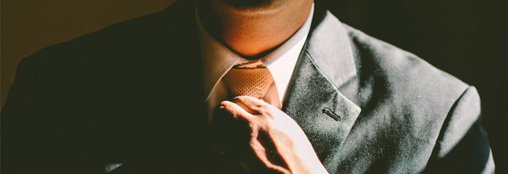 אדם בחליפה מהדק עניבה לצווארו