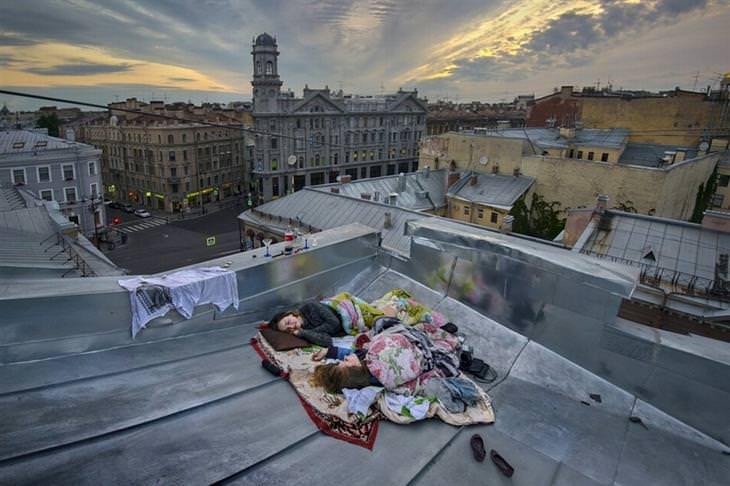 שתי נשים שוכבות על שמיכות על גג של בניין בשעת השקיעה