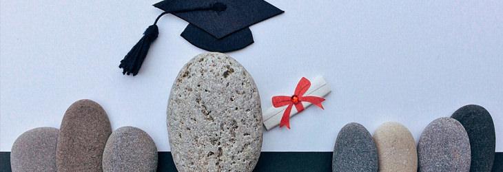 קבוצת אבנים, שמעל לאחת מהן יש כובע סטודנט ותעודה מגולגלת עם סרט אדום עליה
