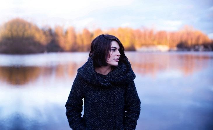 אישה עומדת ומביטה הצידה על רקע אגם