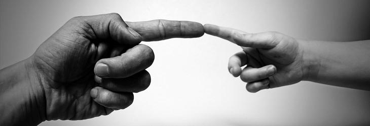 יד של מבוגר ויד של ילד נוגעות אחת בשנייה באצבע