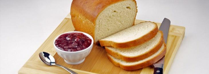 קרש עץ שעליו לחם לבן פרוס, סכין ללחם וכלי עם ריבה