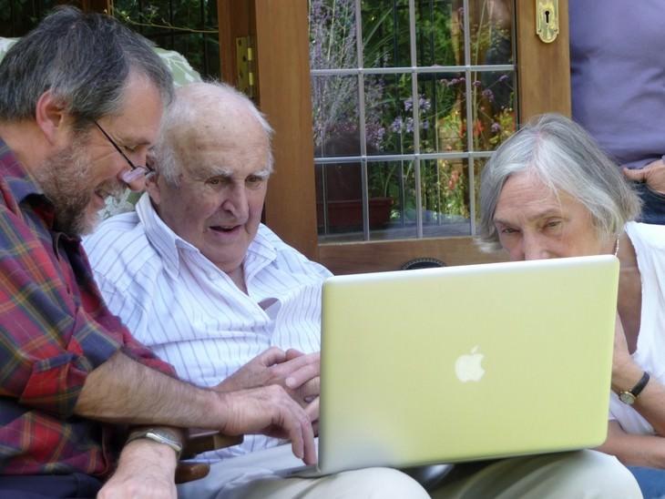 קשיש יושב מול מחשב כשגבר לצידו מסביר לו עליו