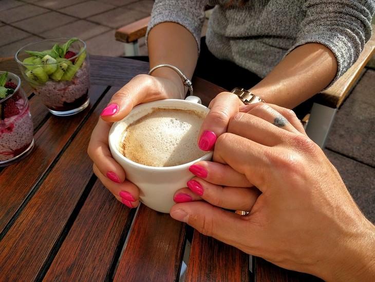 יד של גבר אוחזת בידה של אישה שחובקת כוס קפה