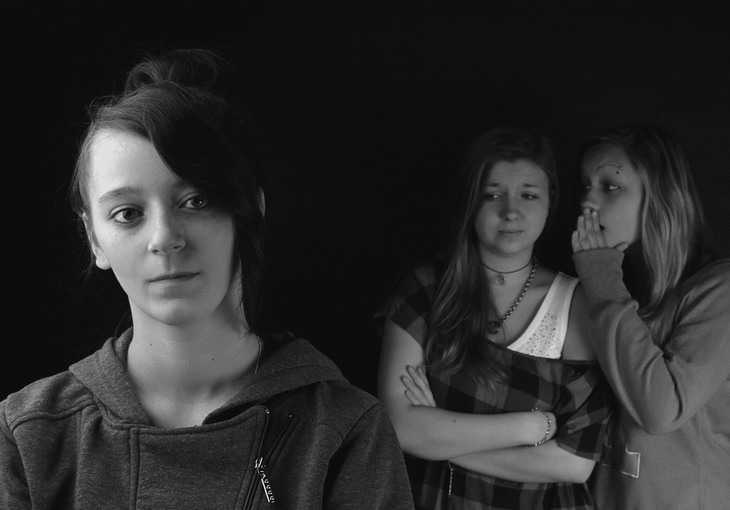 שתי נערות מתלחששות ומביטות על נערה מרוחקת אחרת