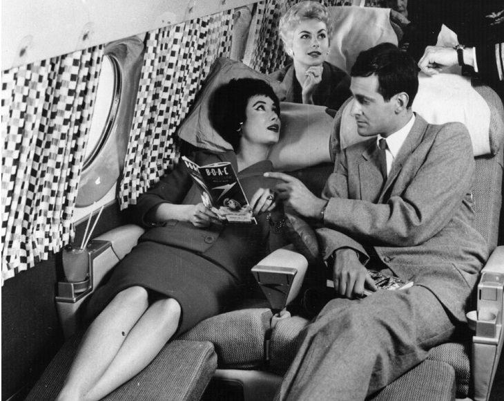 גבר ואישה שוכבים על כורסאות נפתחות במטוס