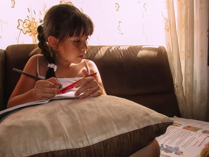 ילדה לומדת על ספה, עם ספרים פתוחים לצדה