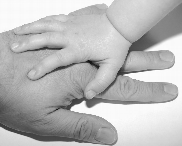 כף יד של ילד מונחת על כף יד של מבוגר