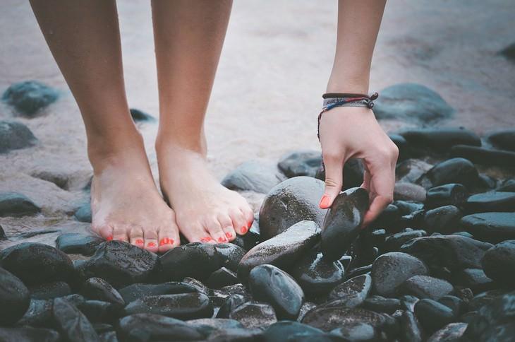 כפות רגליים של אישה שמרימה חלוקי אבנים