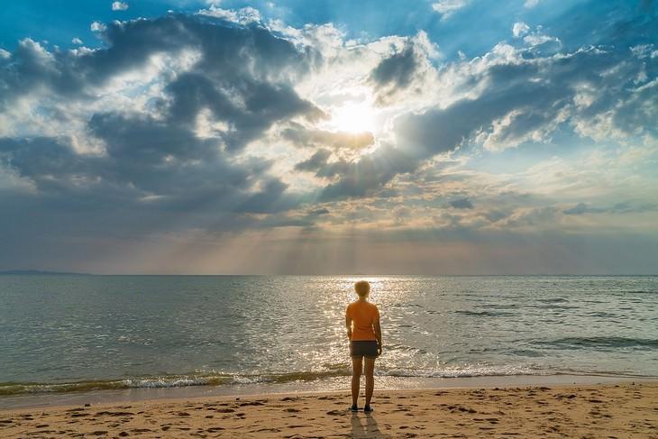 אישה עומדת על חוף הים מול שקיעה