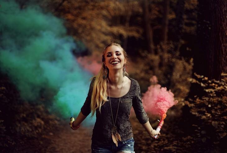 אישה מחויכת מדליקה שני זיקוקי עשן צבעוניים