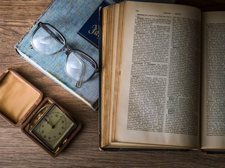 שולחן שעליו ספר פתוח, משקפיים ושעון