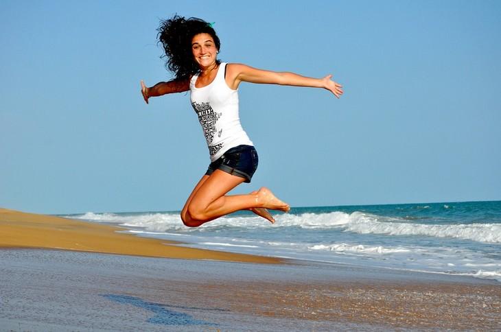 אישה צעירה ומחויכת קופצת על חוף הים