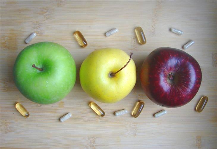 תפוחי עץ וגלולות על משטח עץ