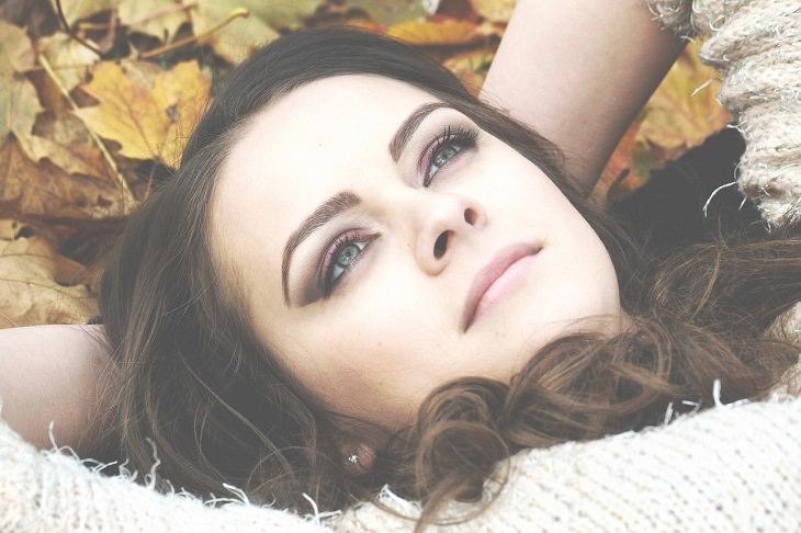 אישה שוכבת על מצע עלים ומביטה מעלה