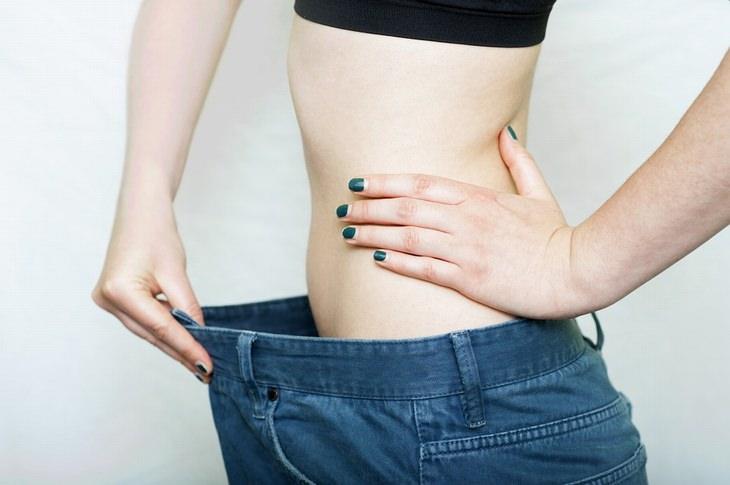 פלג גוף עליון של אישה במבט מהצד - אחוחזת במכנסיים גדולים על מידותיה