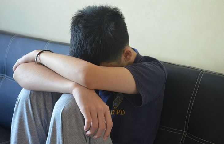 ילד עצוב יושב על ספה