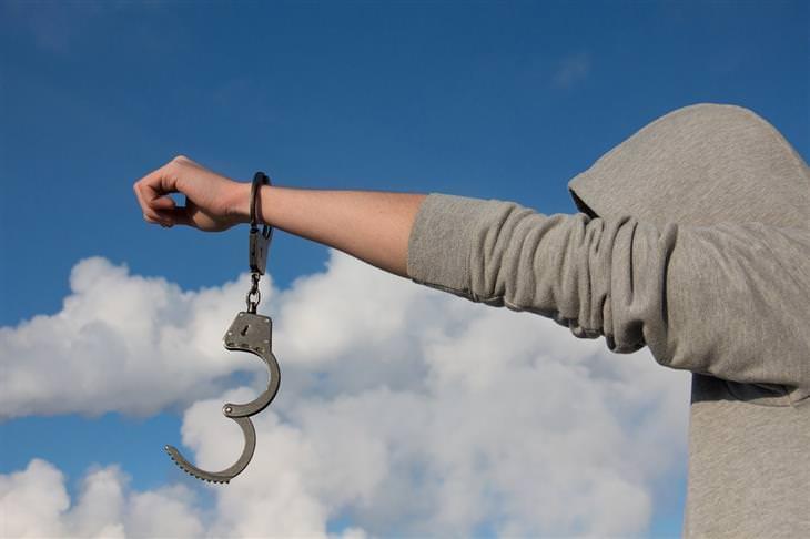 אדם מחזיק את ידו מולו, כשעליה אזיקים