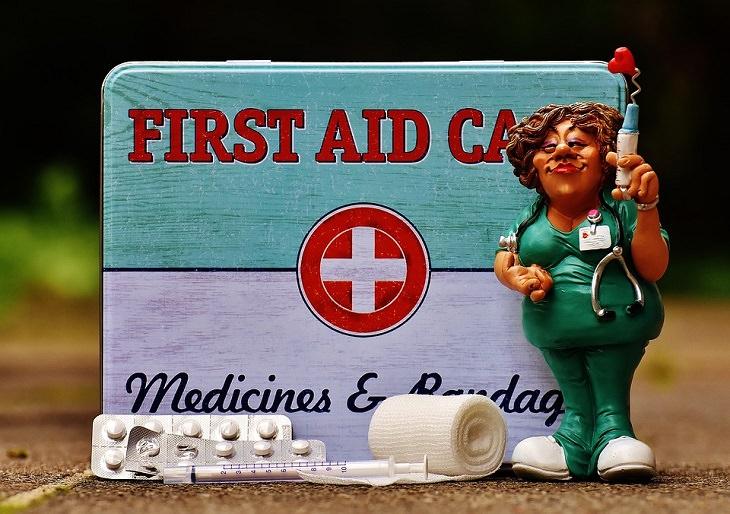 בובה של אחות עם מזרק עומדת לצד קופסה של עזרה ראשונה