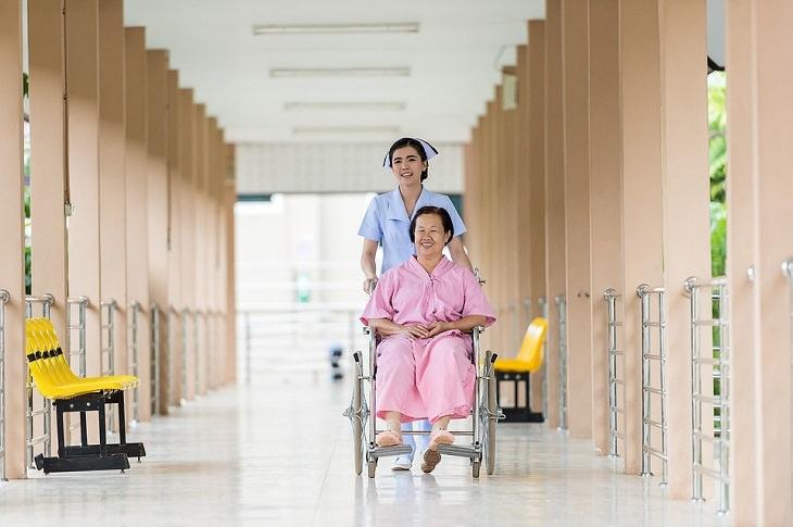 אחות מגלגלת קשישה על כיסא גלגלים
