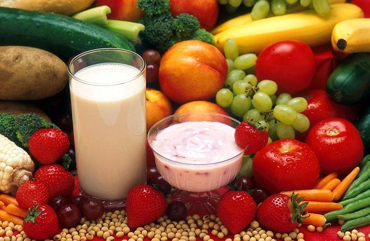 שולחן שעליו פירות, ירקות, כוס וצלחת עם מוצרי חלב