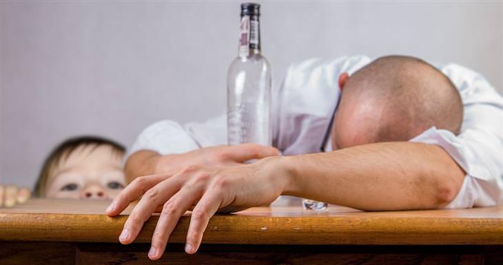 גבר שוכב עם ראשו על שולחן ובקבוק שתייה חריפה בידו. מאחוריו ילד
