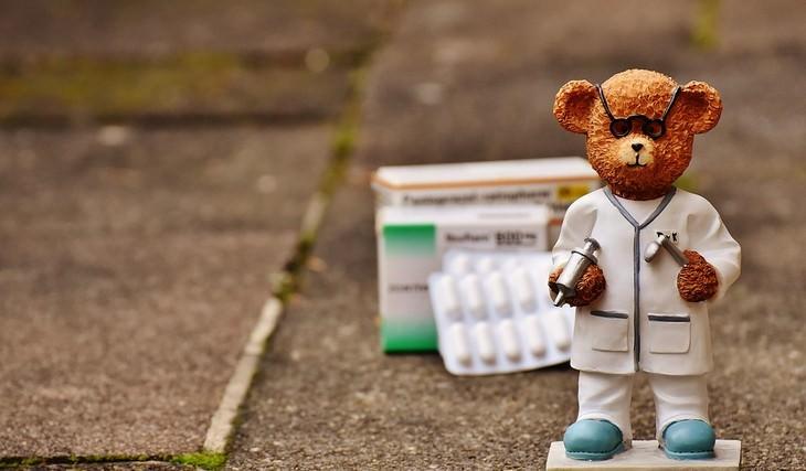 בובה של דוב לבוש כרופא עם תרופות מאחוריו