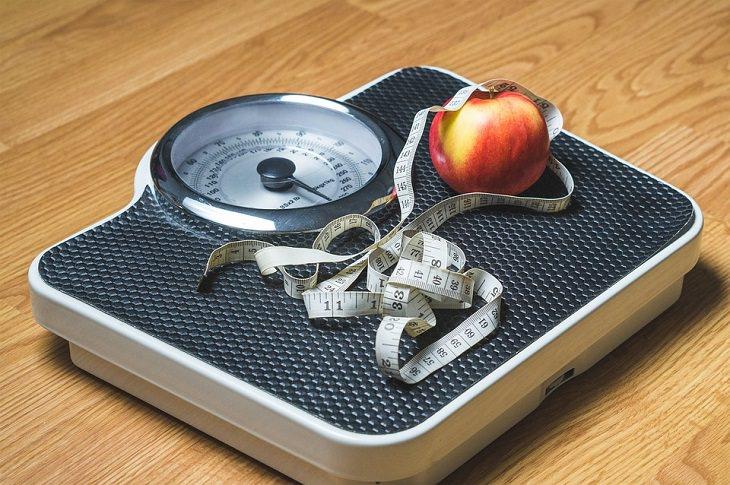 משקל אדם עם תפוח וסרט מדידה עליו