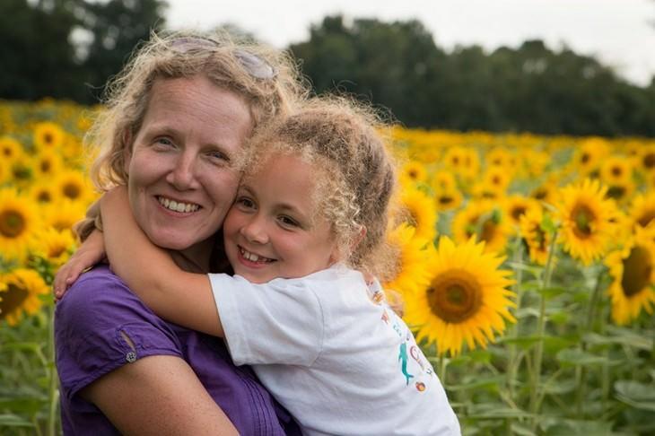 ילדה מחבקת אישה בשדה פרחים