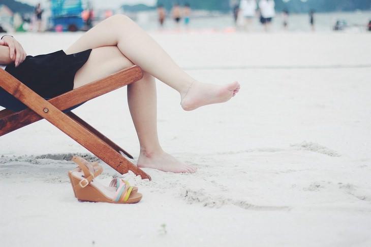רגלי אישה על כיסא נוח בחוף הים