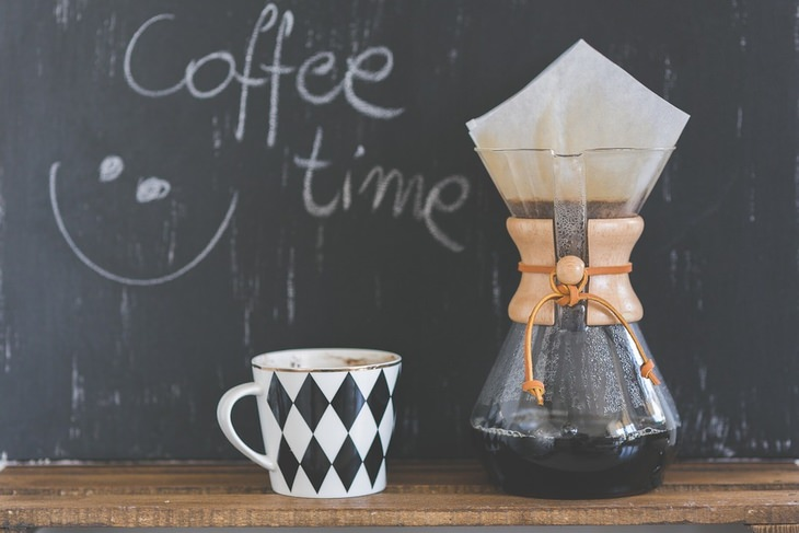"""קנקן קפה מונח ליד כוס, מאחוריהם לוח עם הכיתוב """"זמן לקפה"""" באנגלית"""