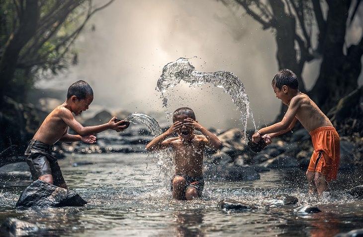ילדים משפריצים מים על ילד אחד