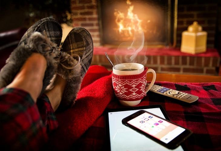 רגליים עם נעלי בית מונחות על שולחן מול אח, לצד כוס משקה חם ושלט טלוויזיה