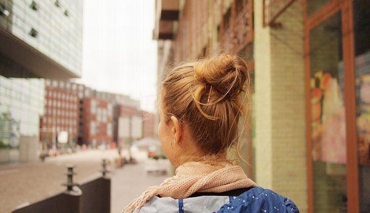 גבה של אישה שהולכת ברחובות עיר