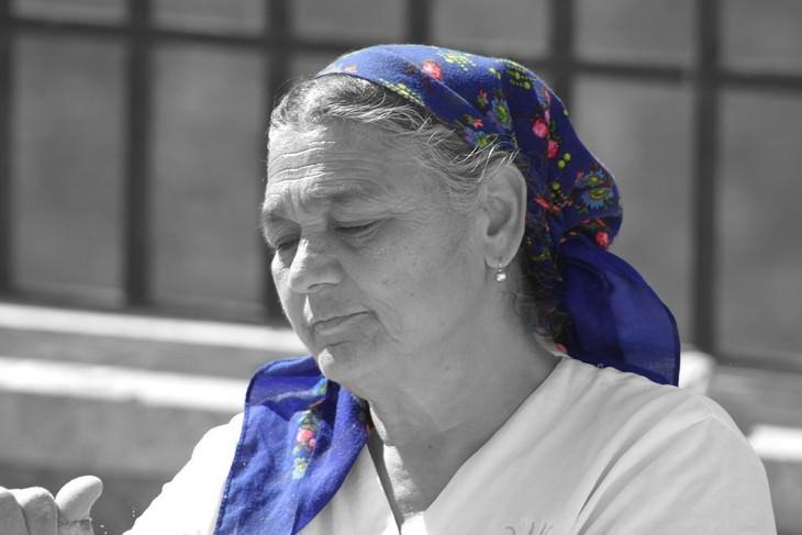 אישה מבוגרת יושבת ברחוב