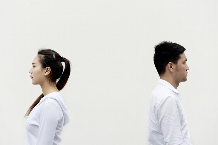 גבר ואישה עומדים גב אל גב ומביטים לכיוונים מנוגדים