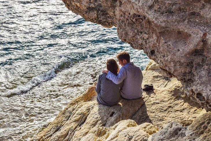 זוג מתחבק על סלע בשפת הים