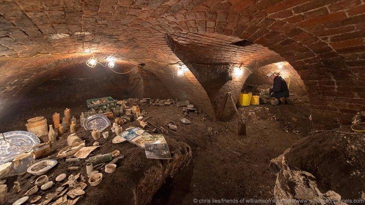 חופר במנהרה לצד ממצאים שנמצאו בתוכה
