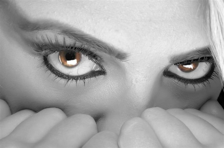 תקריב של עיניים של אישה, שמכסה חצי מפניה עם ידיה