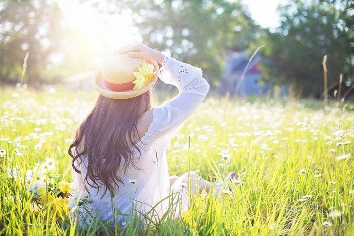 אישה בגבה למצלמה, יושבת בשדה ומביטה אל אור השמש