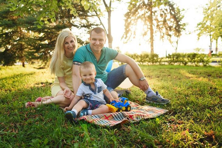 משפחה יושבת ומחייכת על הדשא