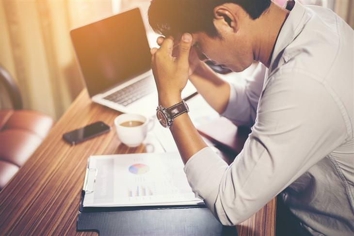 אדם יושב מול שולחן משרדי ומחזיק את ראשו בידיו