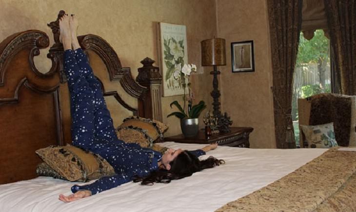 אישה בתנוחה שכיבה עם רגליים על הקיר