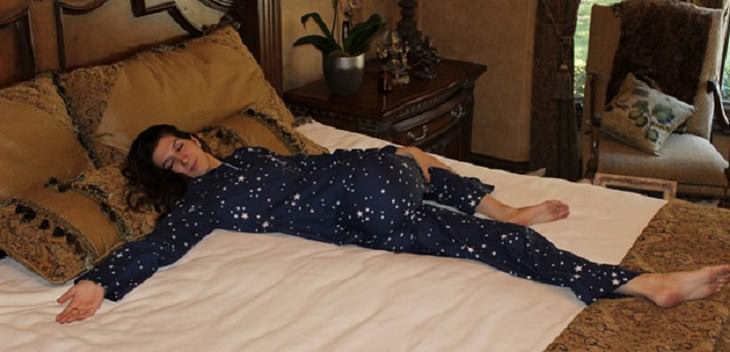 אישה שוכבת בתנוחה סיבובית על מיטה