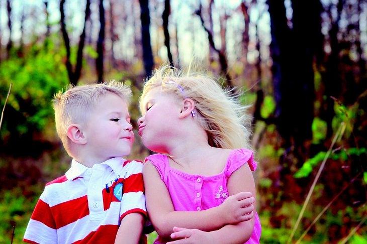 ילד וילדה מתקרבים זה לזה לנשיקה