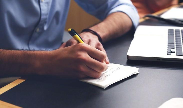 יד של גבר כותבת על נייר לצד מחשב נייד