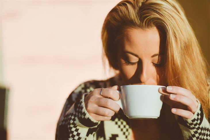 אישה שותה מתוך כוס