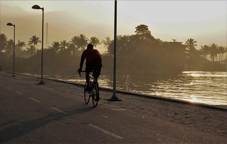 גבר רוכב על אופניים לצד אגם בשקיעה