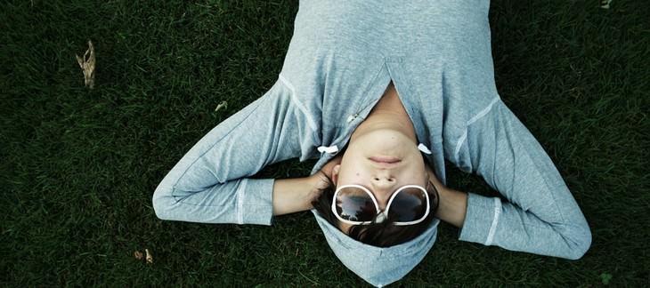 גבר עם משקפי שמש ישן על הדשא כשידיו כרוכות מתחת לראשו