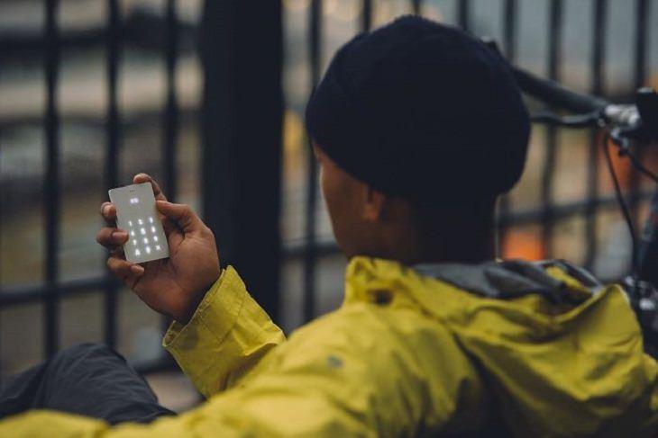 גבר יושב על ספסל ואוחז בטלפון מינימליסטי שנקרא Light Phone